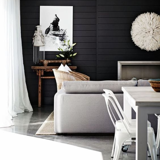 I love this black on the horizontal paneling! It makes the art work pop, the polished concrete floors sing, and the browns in the side table and cushions look rich and vibrant.