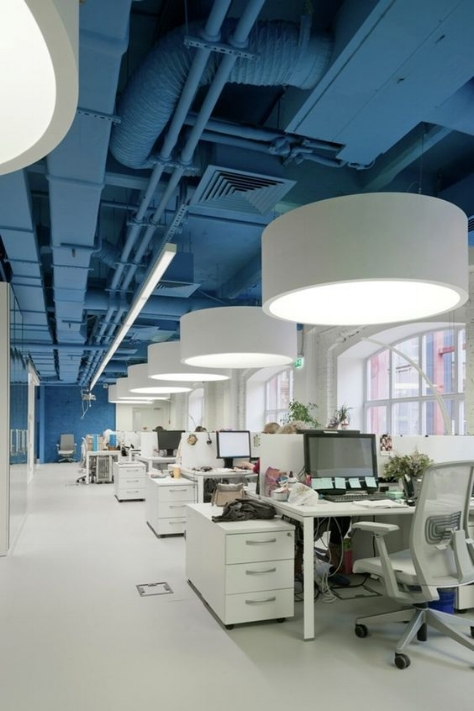 I love how this all white office uses a bright blue ceiling to add a playful element to their workspace in an unconventional way. The way it extends all the way down to one wall makes this medium sized office look much longer than what it actually is - a great example of how darker colours can make your space look larger!