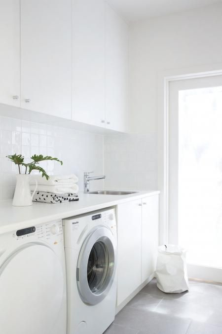 I adore this all white laundry. Clean and bright, even though it is a very small space it doesn't feel cramped. The white tile splash back gives some light reflection which is an added bonus in small spaces. Going for a light floor tile is ideal in this situation as it doesn't draw attention to how small the floor space actually is.