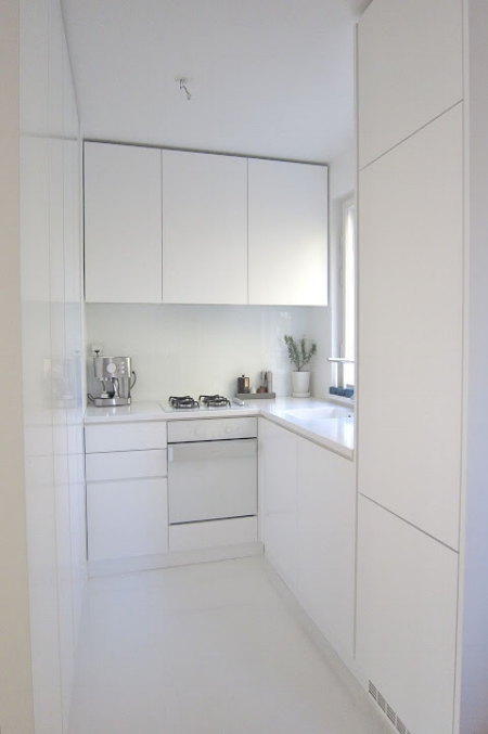 Now this is small design! This apartment kitchen looks as big as it possibly can by using an all white scheme. White glass splash back reflects light, and a white oven front means there is no visual breaks in the cabinetry which is so important for visual flow!