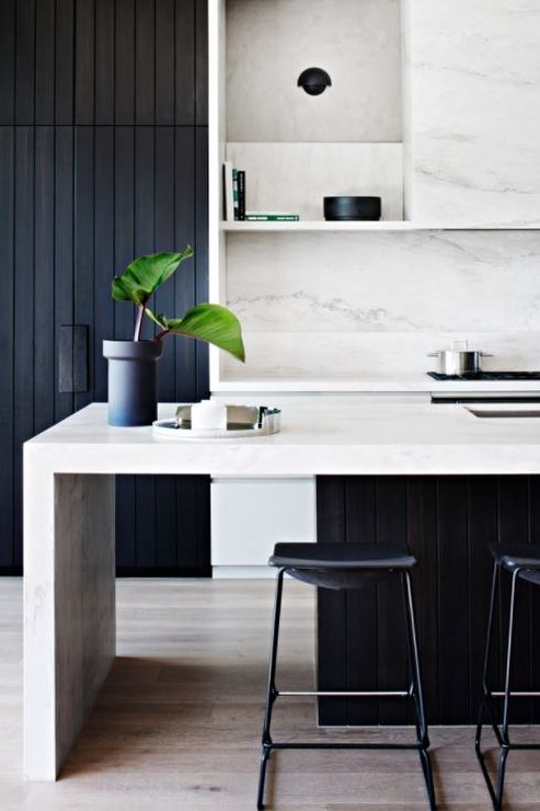 A bold Black and White look with chunky bench tops, softened with natural marble pattern. The 'see through' island end provides a moment of light relief from an other wise heavy space.