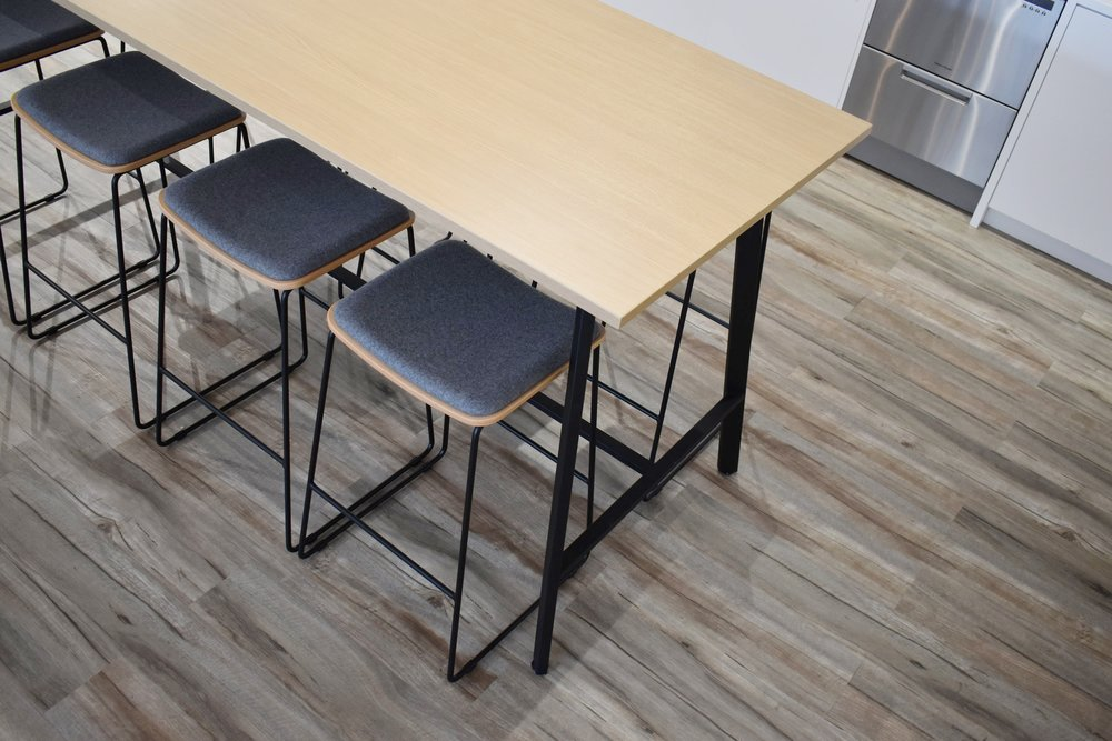 Custom bar leaner and stools were brought into the kitchen space so people from different offices could have a moment to interact. This is a great alternative to individulal tables and chairs.