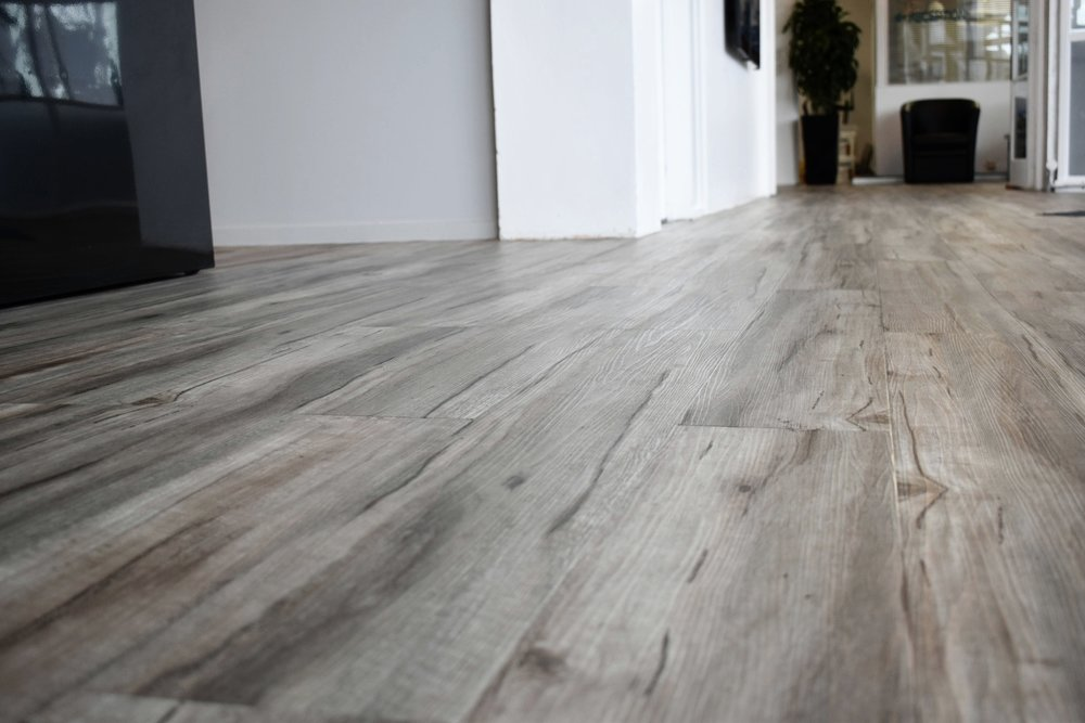 The wood plank vinyl floor is carried throughout the entire entry, reception, communal lounge, kitchen and hallways to give a more continuous, cohesive aesthetic.