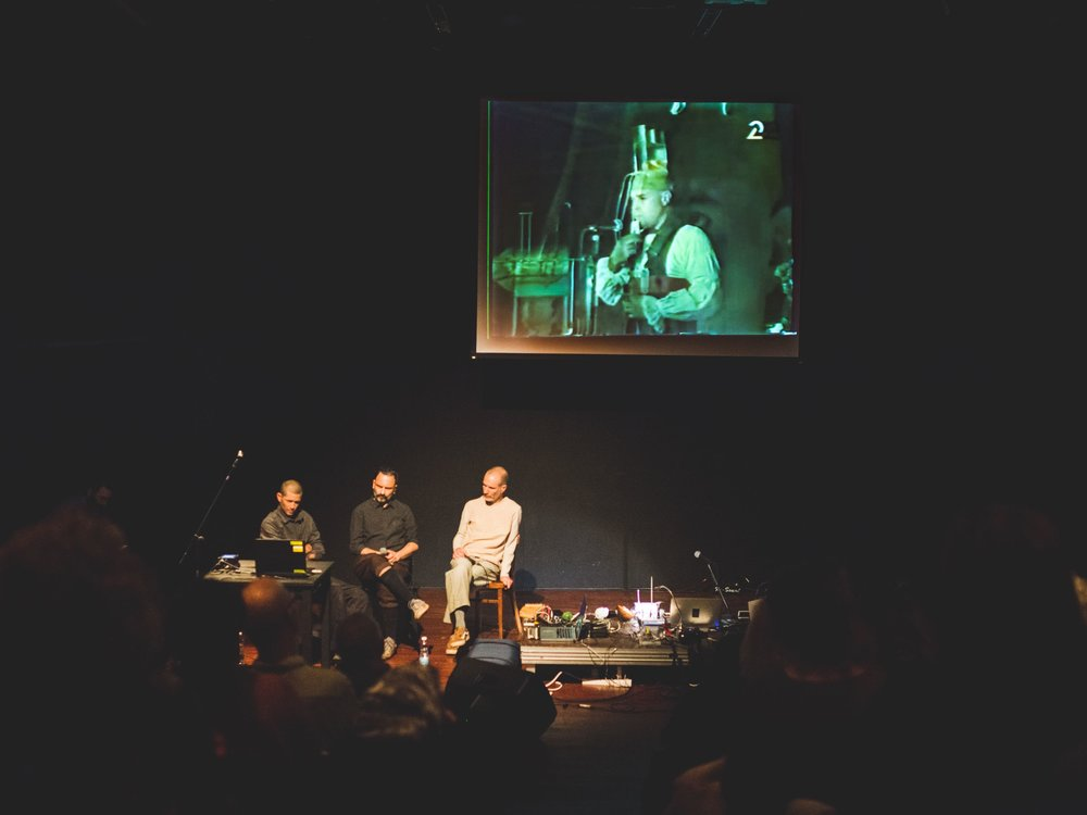 "Ohad Fishof, Yishai Adar, and Benia Reches and on the screen the performance video of ""Panta Rai"" in the background. Uri Katzenstein performed in the ensemble ""Panta Rai"" with Yossi Lederman of blessed memory, at the Roxanne Club in Tel Aviv in 1991."