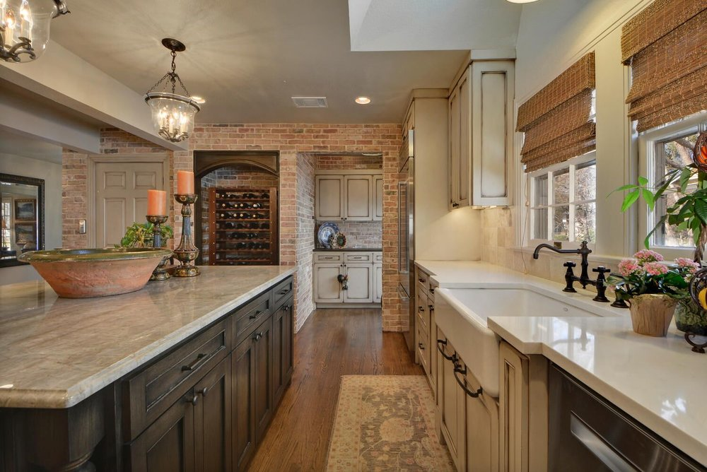 Multi-color kitchen cabinets with cabinet pull handles in center island