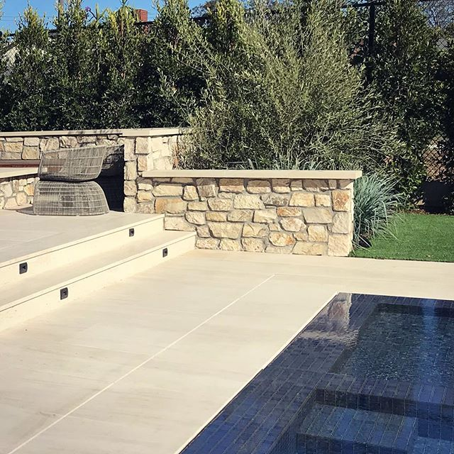 Navy blue pool tile and warm limestone in Mar Vista