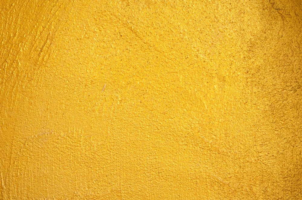 Textured wall with yellow paint finish.