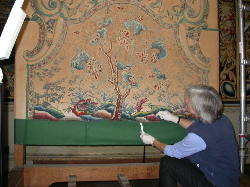 Kate Gill in the process of conserving the lower headboard