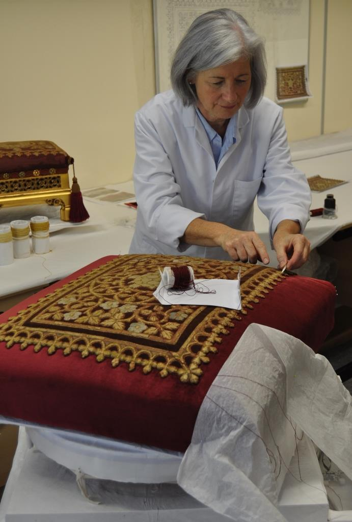 Kate Gill attaching the conserved embroidered panel to the newly covered upholstered seat unit