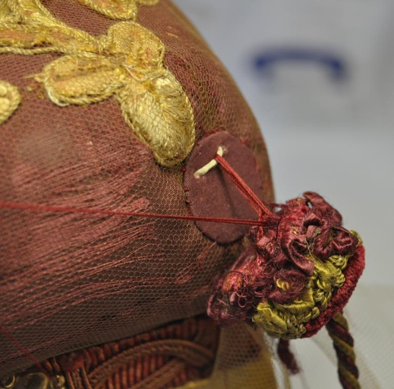One of the tassels in the process of being attached to the conservation support
