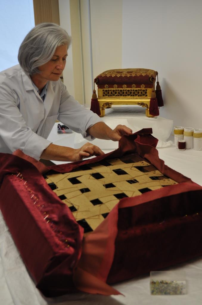 Kate Gill re-covering the seat unit with new velvet, using conservation techniques that minimise damage to the wood frame and existing upholstery