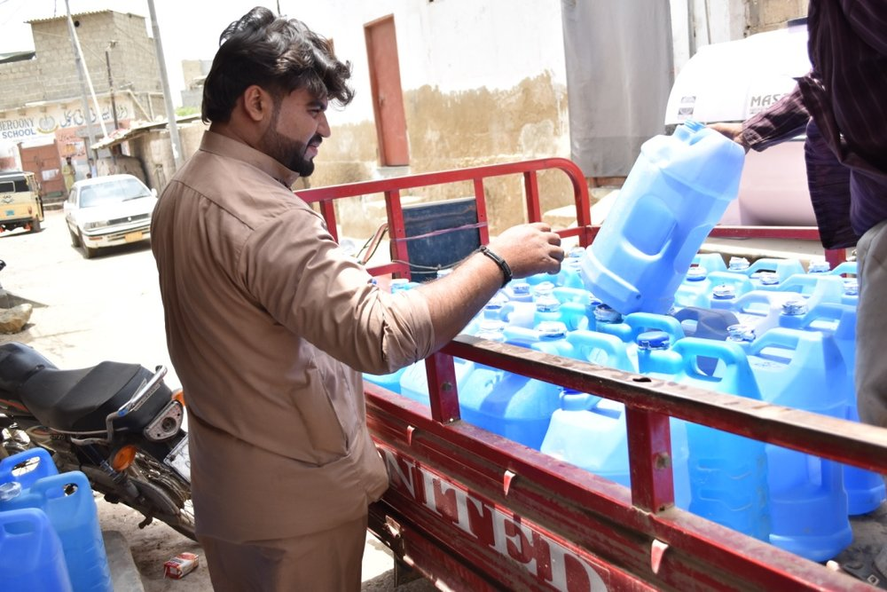 Zia Rahman, one of Sukoon Water's employees, delivers safe drinking water to one of our distribution points