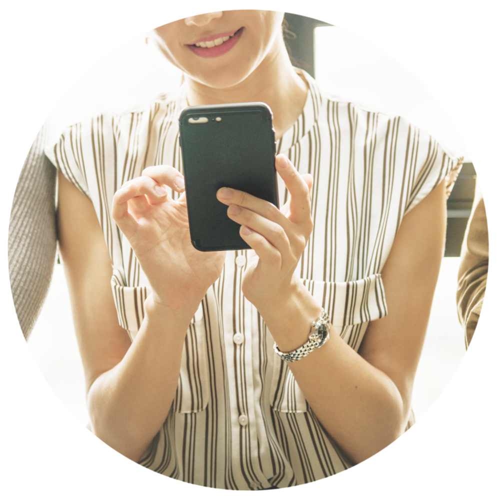 Woman smiling and looking at phone.