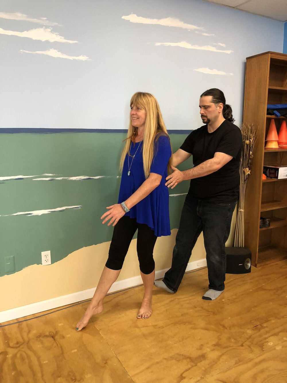 "Standing and walking pathways are explored. The practitioner standing behind the client listens in, offering gentle cues. The concept ""Somatic Empathy"" is a work here as the practitioner communicates efficient movement to the client through touch and movement."