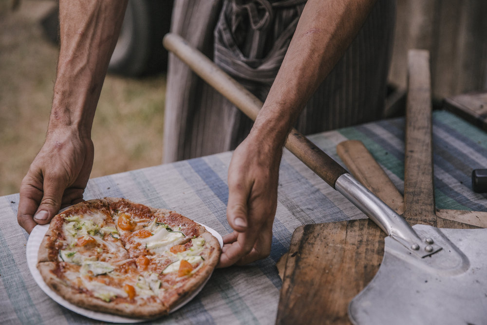 Owner, James Ferraris, serving a personal wood-fired pizza during a casual wedding rehearsal on Orcas Island, WA.