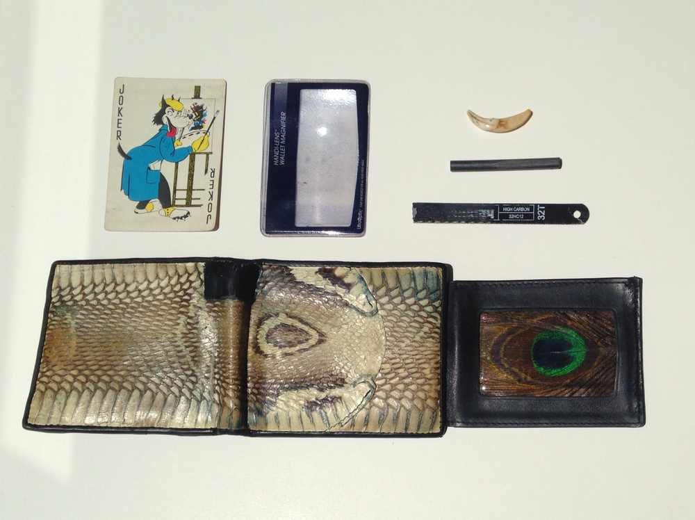 Untitled (Wallet II),  2015 Cobra skin wallet, duct tape, peacock feather, playing card, fresnel lens, coyote incisor, magnesium rod, length of hacksaw blade 13 x 8.5 inches
