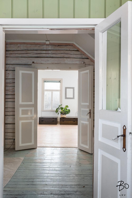 Talo on täynnä sympaattisia yksityiskohtia, katsokaa nyt noita ovia ja vanhoja kahvoja. Tässä näkymä kuistilta olohuoneeseen.