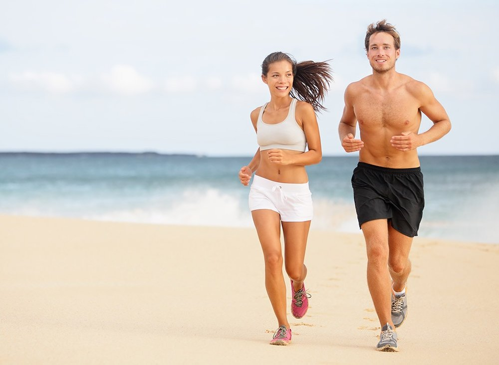 Depiction of a happy and fit young couple jogging at the beach. An Example of Aurum Fitness Customers