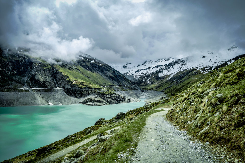 Hey, guys this week we will be talking about my best photo, which was taken at Lac de Moiry in Switzerland. This is the best location I have ever shot at. It is truly breathtaking. We had been planning this hike for the last week. We chose this specific day due to the weather, it was supposed to be bright and sunny. Sadly, that was not the case. It was very cloudy and it was even drizzling. We decided to keep walking through the rain. Then out of nowhere it stopped raining. We quickly set up and started to shoot. We found as many different compositions as possible while it wasn't raining. This is the photo that came out of it. But then it started hailing. We started sprinting to the coffee shop next to the trailhead. I hope you love the shot. If you would like to purchase a digital version of the shop go to the digital section. PRINTS WILL BE AVAILABLE SOON!!!