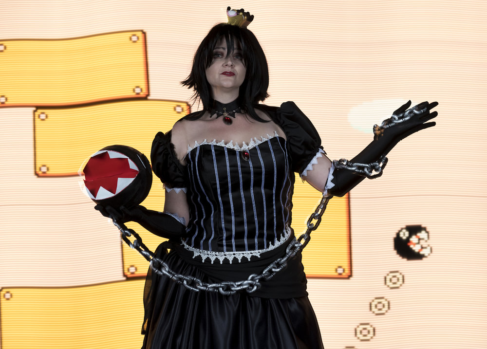 Allybelle Cosplay cosplaying as Ann4rt's Chompette posing with a Chain Chomp with a scene from Super Mario Brothers 3 light painted behind her