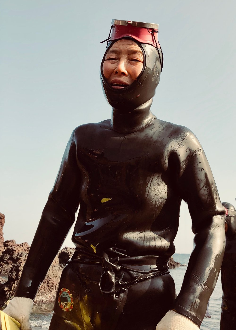 female diver in wetsuit standing on the beach near rocks