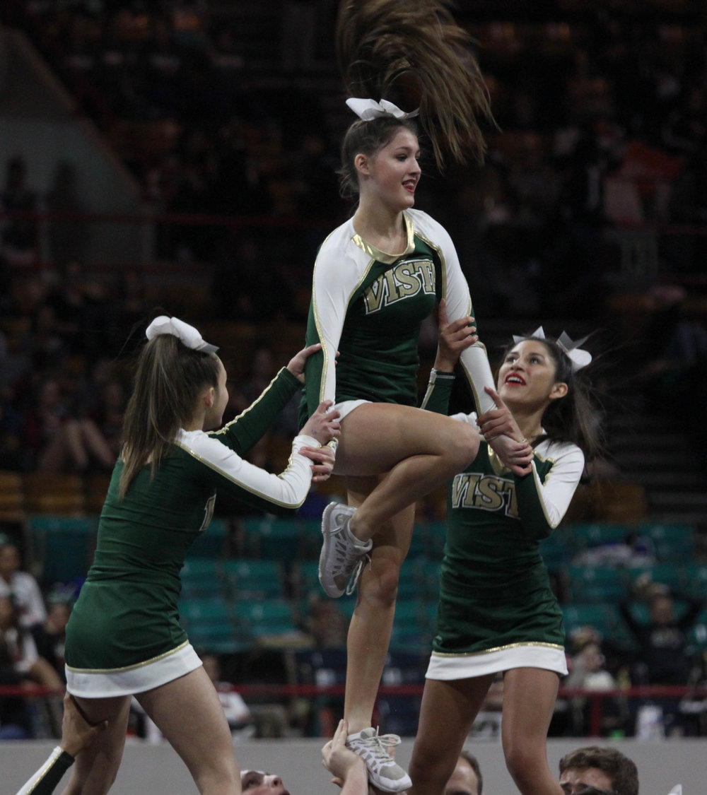 Sophomore Taylor Black is flipped during a routine at the Cheer State Competition.