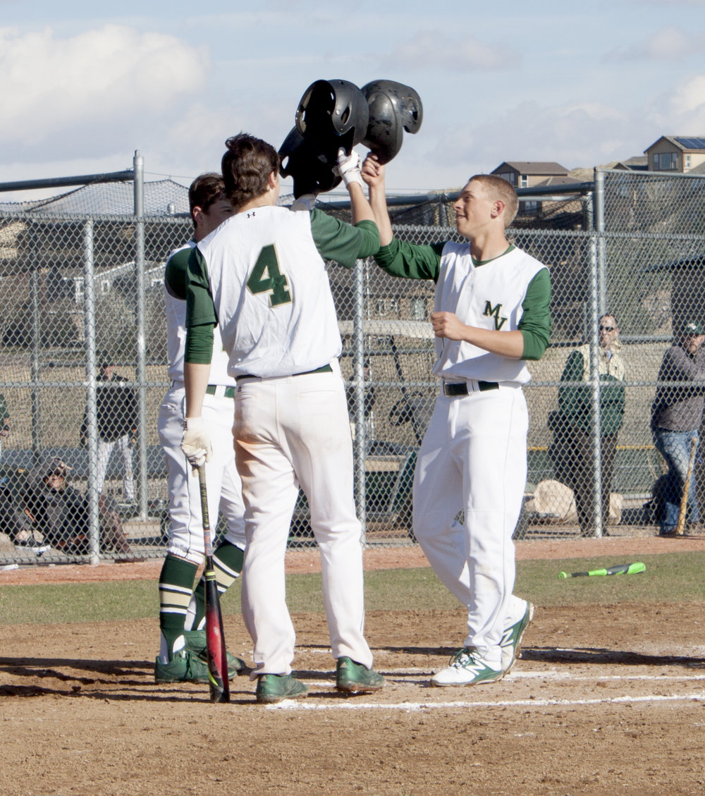 Senior Cole Blachford is congratulated by his teammates after hitting a home run.