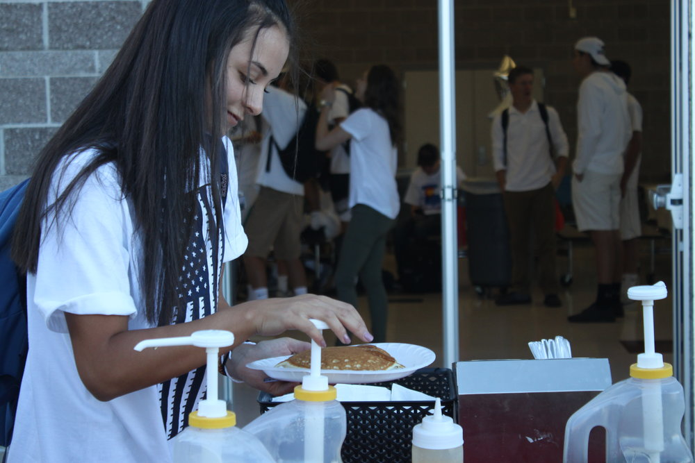 Senior Maisie Paulson puts syrup on her pancake at the annual FBLA and DECA breakfast.