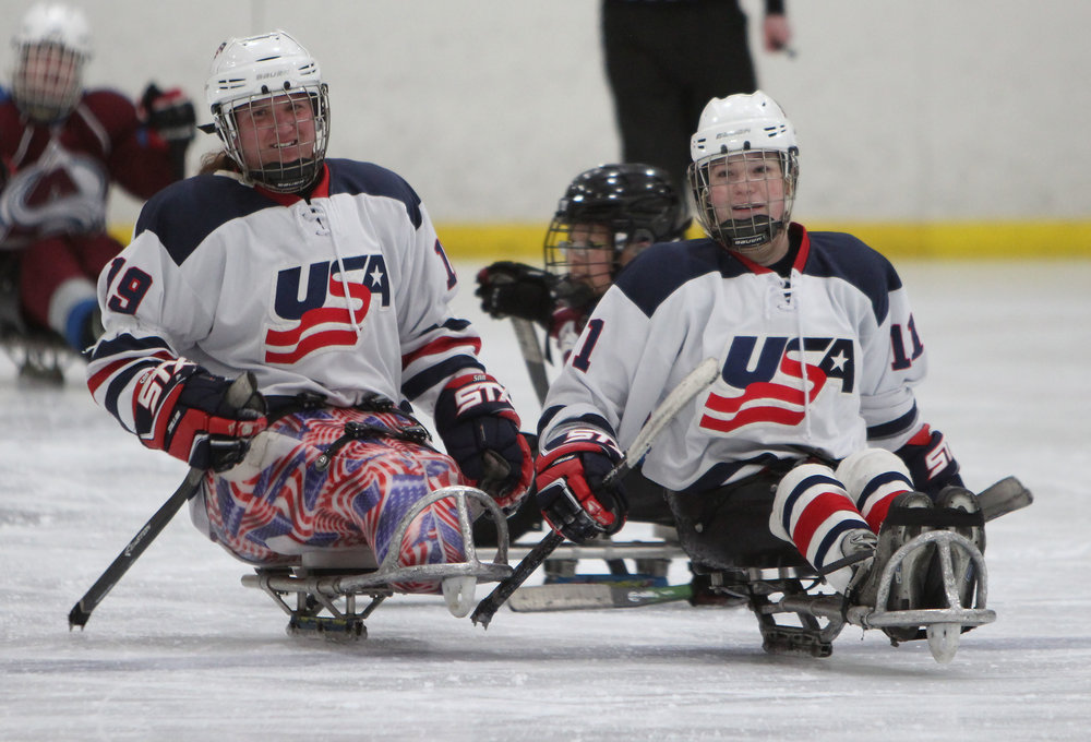 US Women's sled hockey teammates celebrate after a goal in a game against the Colorado Avalanche.
