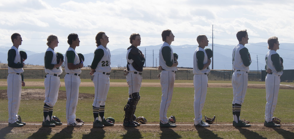 Vista varsity baseball players line up for the National Anthem before the biggest game of the season.
