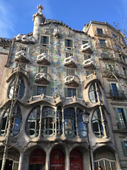 Billedet viser Casa Batllé på Passeig de Gracia. Gaudi foretog en gennemgribende renovering af bygningen i 1904 – 1906. Facaden er belagt med keramiske fragmenter og ligner en slags fiskeskel. Balconerne er formet som slangehoveder, søjlerne er formet som knogler med dekorationer, som forestiller grøntsager, og på taget ses ryggen af en drage.