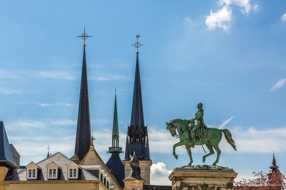 Summer in Luxembourg- The Guillaume II statue on Knudler with the rooftoops of the Notre-Dame Cathedral in the background on a sunny spring day - Rooftop Rider