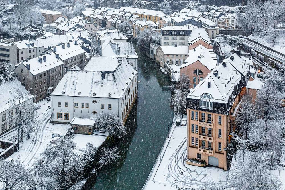 Winter in Luxembourg - Luxembourg's Grund and Alzette river on a Winter morning with falling snow - Old Man Winter