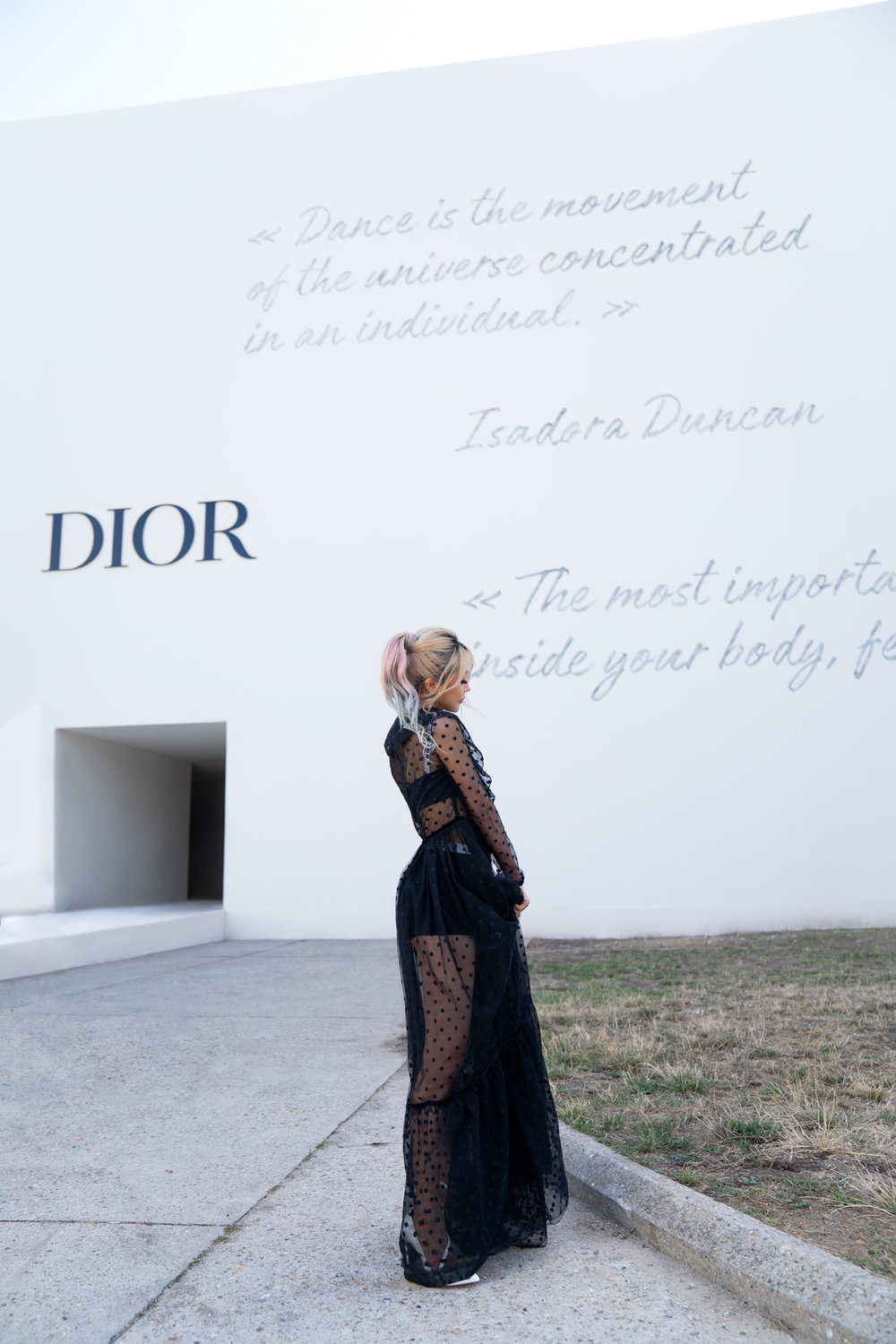 Wengie poses in front of the grand entrance to the Dior show