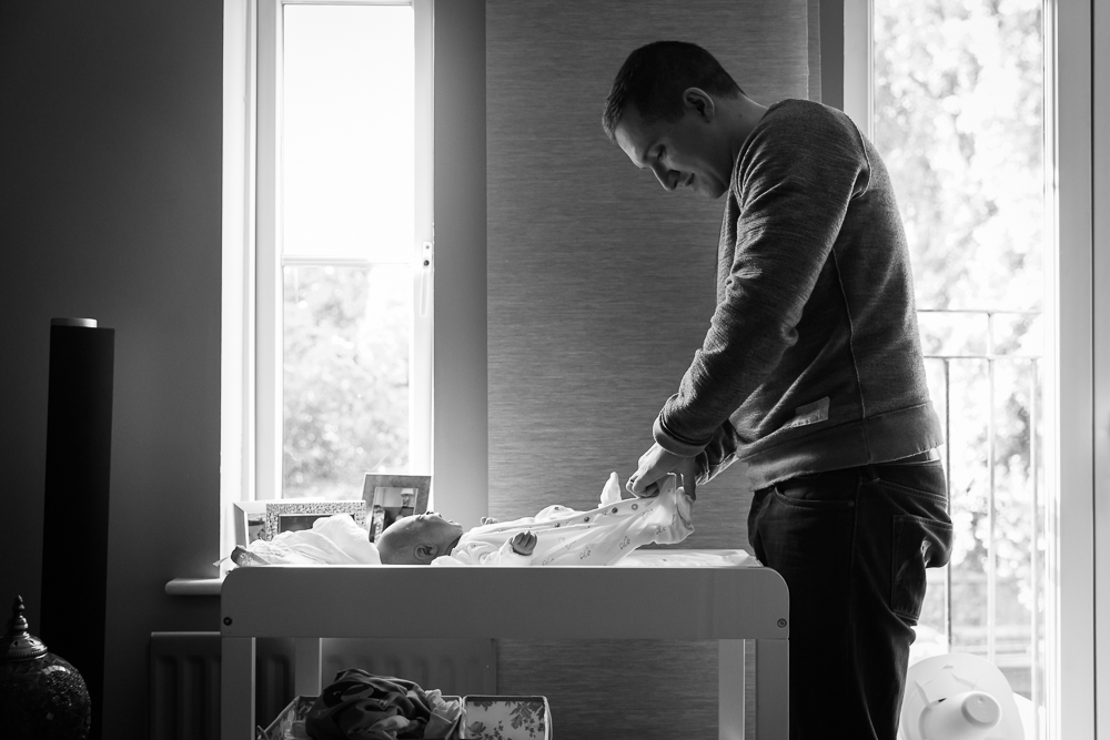 New father changing his crying newborn baby boy during a newborn in home session in black and white