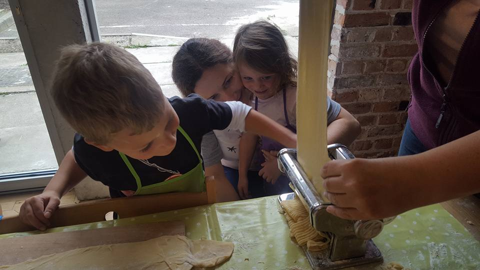 Children making pasta with a pasta machine at The Healthy Families Programme.