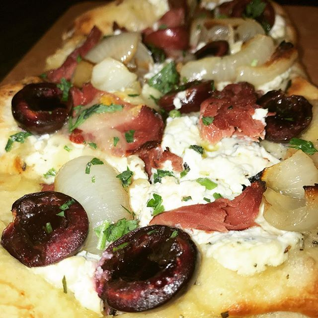 Stop on by for our Chef's Seasonal Flatbread! Mesquite smoked Duck breast, whipped ricotta infused with Thyme & local Bing cherries🍒 Pair it with $5 draft beer, $5 specialty cocktails, & $5 wine by the glass!