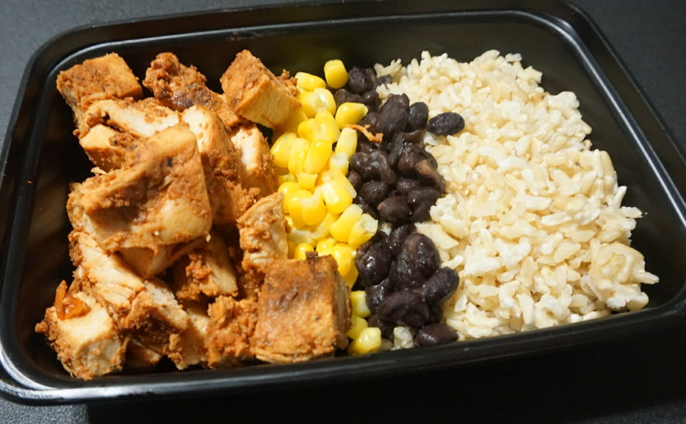 Chipotle Chicken Bowl  A delicious blend of chipotle flavored shredded chicken, black beans and corn, served over a bed of brown rice. Served with our special green salsa.