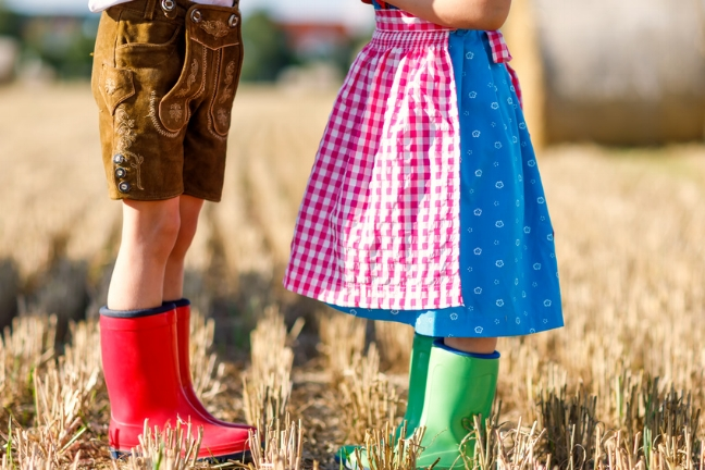 Two kids in traditional Bavarian costumes and red and green rubb
