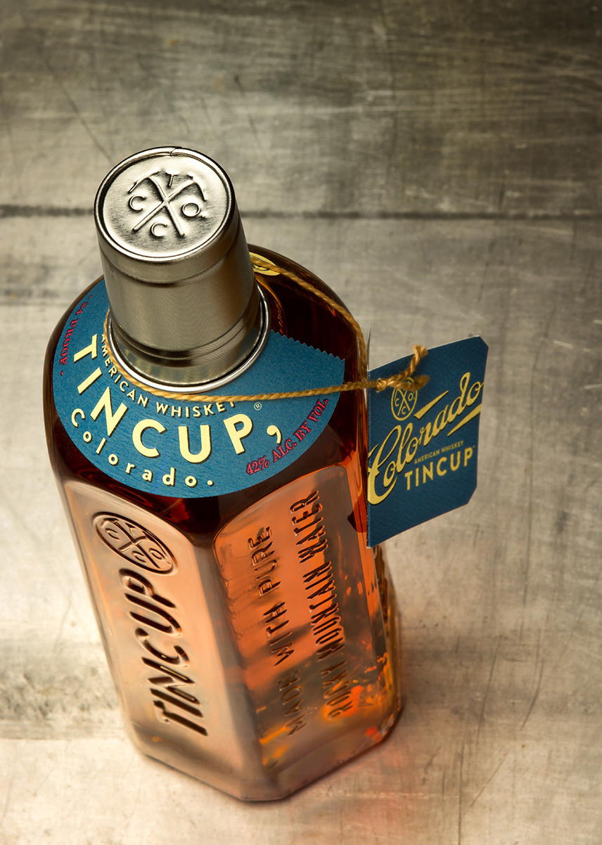 Tincup whiskey bottle photographed on old sheet metal