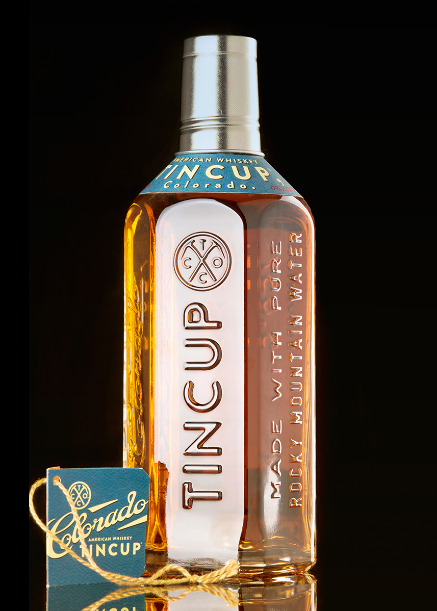 Tincup whiskey bottle photographed on black background