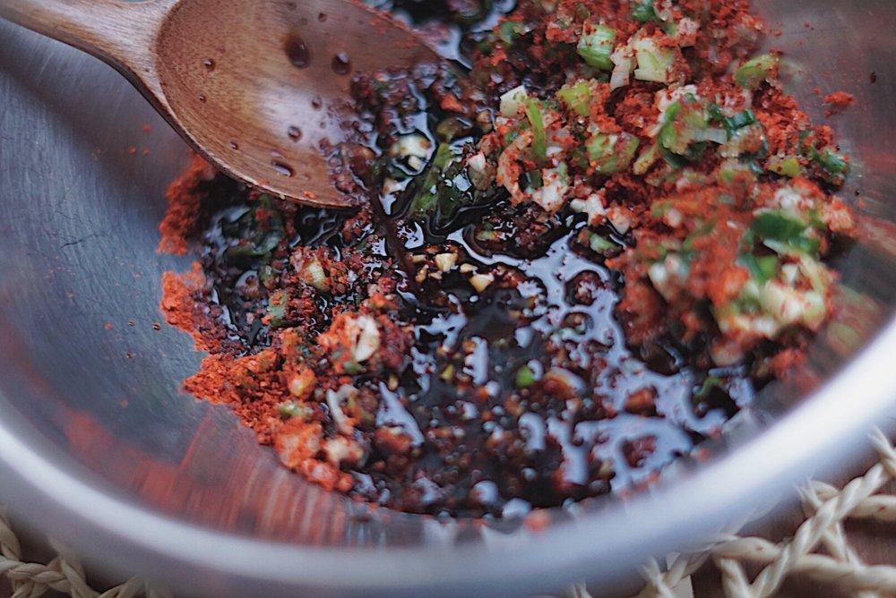 Combine garlic, green onions, pepper, soy sauce, gochugaru and sugar and mix well. -