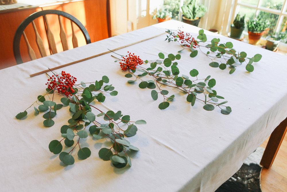 Step 1 - Trim Eucalyptus branches so that instead of one large branch there are several smaller branches. Then layout how you want your garland to look. This will make the next step easier and your garland will have a more cohesive look.