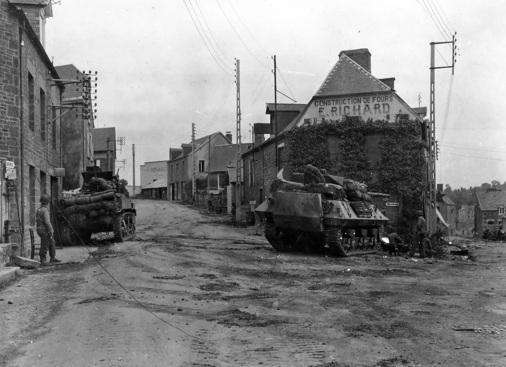 2nd Armored Division M5 Stuart and M10 Wolverine of the 702nd Tank Destroyer Battalion cover approaches into Tesey Sur Vire, France, 1944.