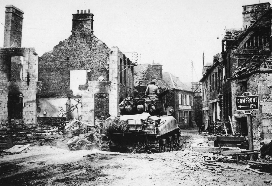 2nd Armored Division M4A1 crosses the central bridge of   Lonlay L'Abbaye, 15 Aug 1944.
