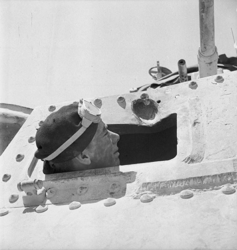 The driver of a Grant tank takes a closer look at a gouge in the armour plate made by a 50mm anti-tank round, Libya, June 1942. IWM photo E 13261