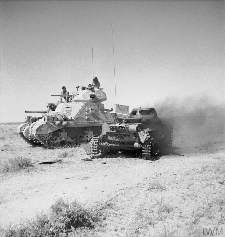 A Grant tank passes a burning German PzKpfw I tank, 6 Jun 1942. IWM photo E 12920