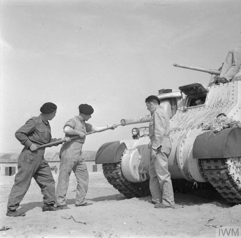 The crew of a 3rd Royal Tank Regiment Grant tank clean the vehicle's sponson-mounted 75mm gun, 20 Feb 1942. IWM photo E 8580