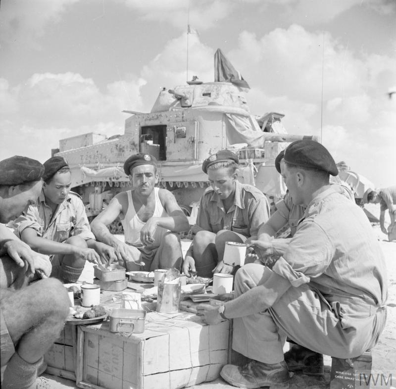 A Grant tank crew of the Staffordshire Yeomanry, 8th Armoured Brigade enjoying lunch beside their tank, 24 Oct 1942. IWM photo E 18405