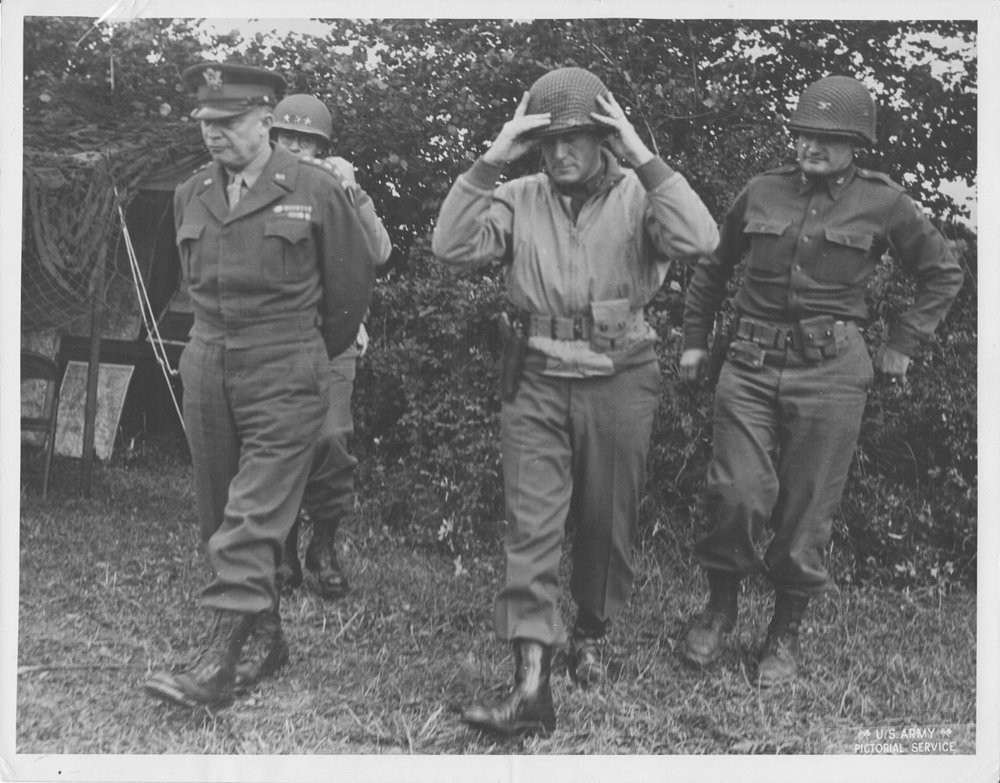 "Major General Brooks walking with General Eisenhower, Lieutenant General Bradley and Colonel Palmer.   The division landed on Omaha Beach on June 9, 1944. The 2nd Armored Division was committed immediately.   Brooks was cited for gallantry in action during the period August 2 to 6 for making repeated visits to forward elements of his command. Exposing himself to hostile observation and fire, he expedited the commitment of the division and personally assisted in the organization of continuing attacks by subordinate units in assault on enemy strong points. That display of gallantry and leadership, without regard to his personal safety, earned for him the Silver Star. Brooks personally pushed the 2nd Armored Division into being among the first Allied divisions on Belgian soil and was the first Allied division commander to enter that country by assault. An incident during the drive into Belgium occurred when a corps staff officer came to Brooks' 2nd Armored command post and told the general that he had a mission for the division that he feared was impossible—to be in Ghent in two days. The staff officer's eyes bugged out when the general said, ""Tell the corps commander it's in the bag. We'll be there."" After the officer departed, Brooks turned to his chief of staff,  Colonel   Charles D. Palmer , and said, ""Where the hell is Ghent?"" They made the objective behind enemy lines and outside their operational zone, with hours to spare."